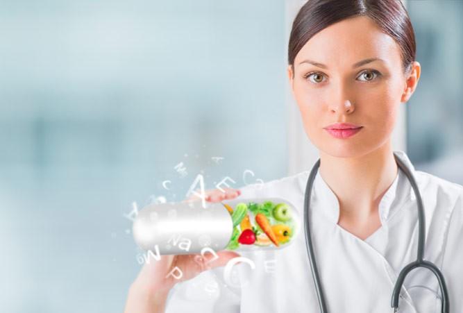 врач с капсулой витаминов