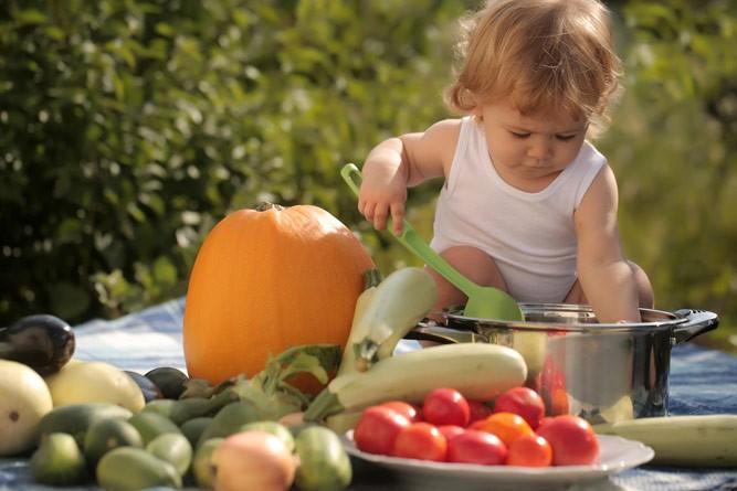 малыш с овощами на природе