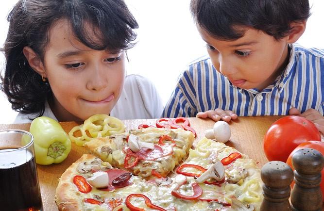 дети кушают пиццу с грибами