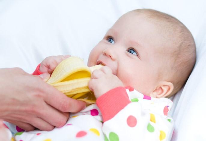 малыш пробует банан