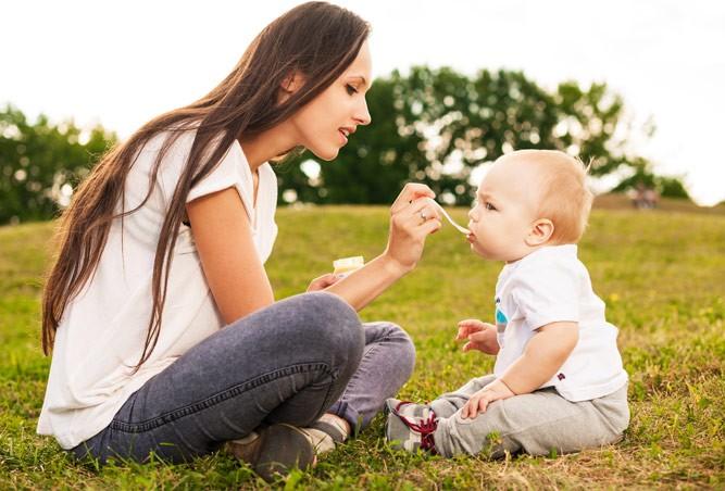 мама кормит малыша на свежем воздухе
