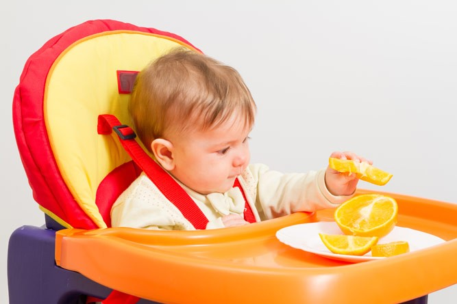 малышка в детском стульчике лакомится апельсином