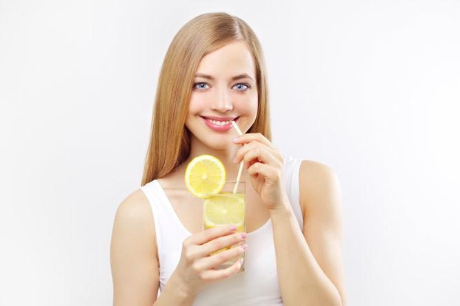 молодая мама пьет напиток с лимоном