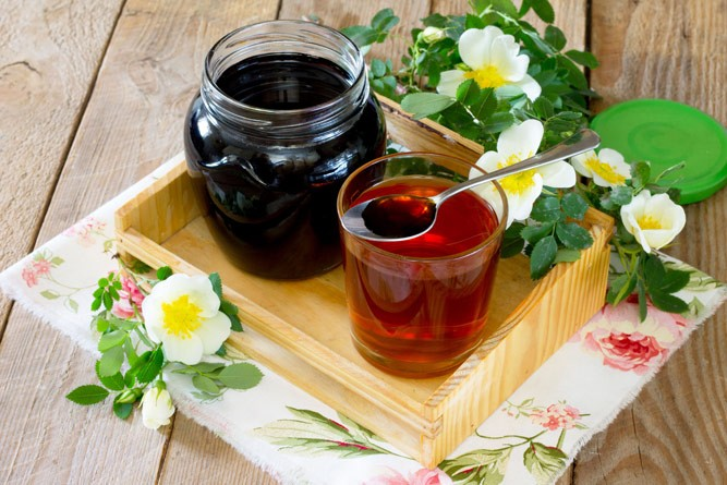 сироп шиповника в ложечке с чаем