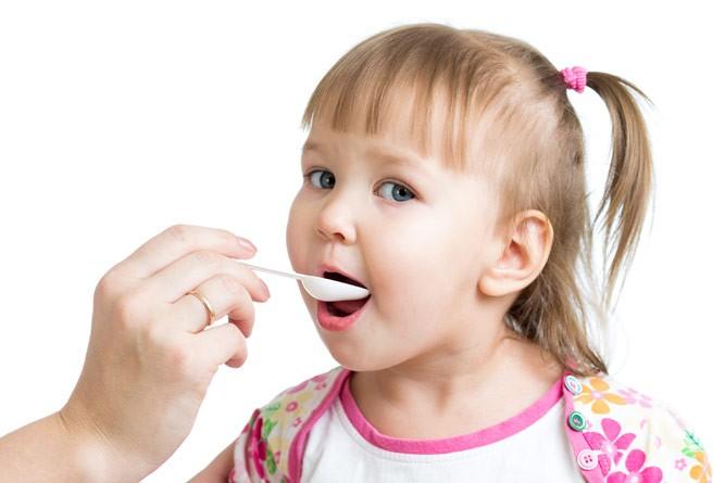 четырехлетняя девочка принимает жидкие витамины