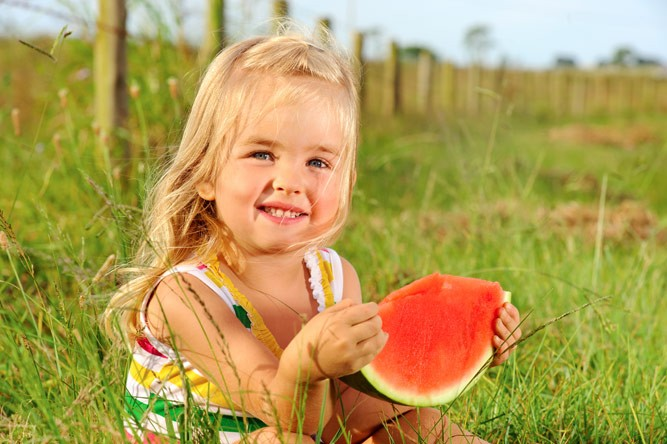 девочка держит в руках дольку арбуза