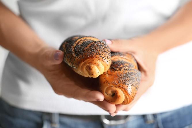 свежие булочки с маком в руках