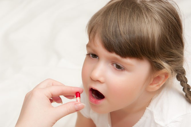 Пятилетняя девочка принимает витамины с маминых рук