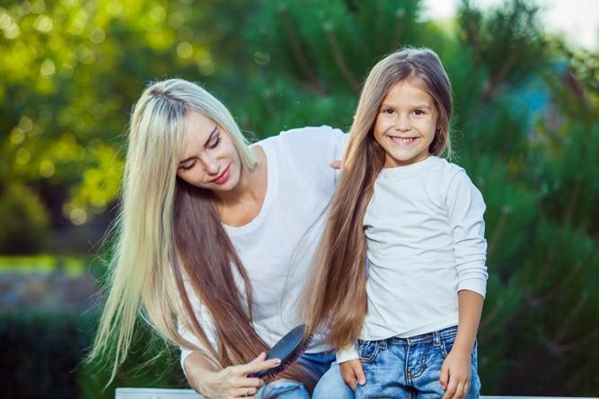 Мама расчёсывает длинные волосы дочке
