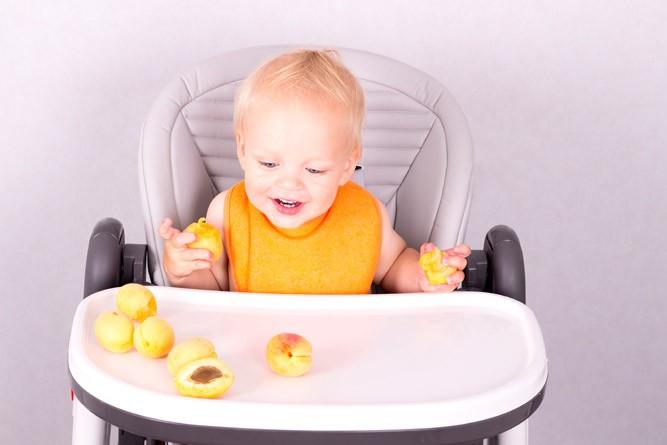 Ребёнок впервые пробует абрикосы
