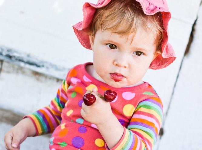 Малышка с веточкой черешни в руках