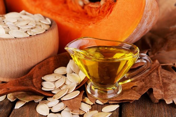 Чашка с маслом на фоне тыквы и рассыпанных тыквенных семечек