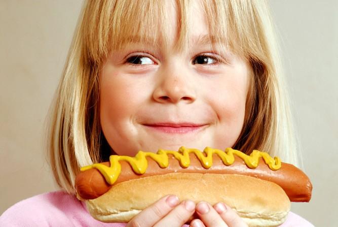 Маленькая девочка ест хот-дог с горчицей