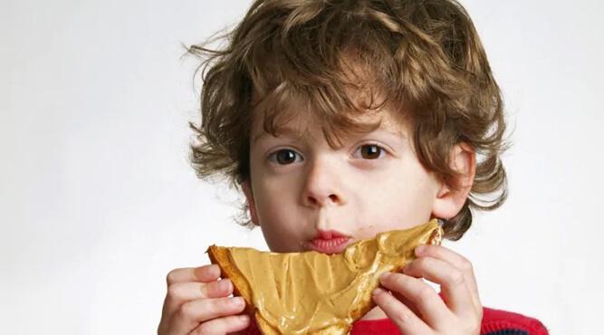 мальчик лакомится бутербродом с арахисовой пастой