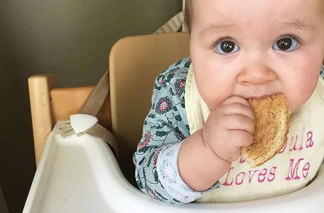 малыш пробует арахисовую пасту