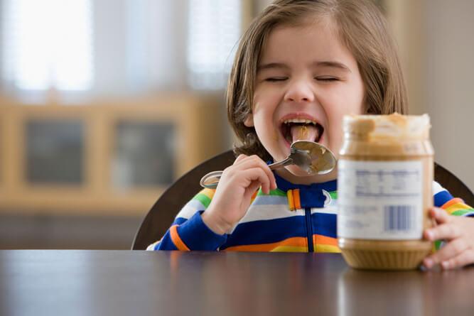 ребенок ест арахисовую пасту